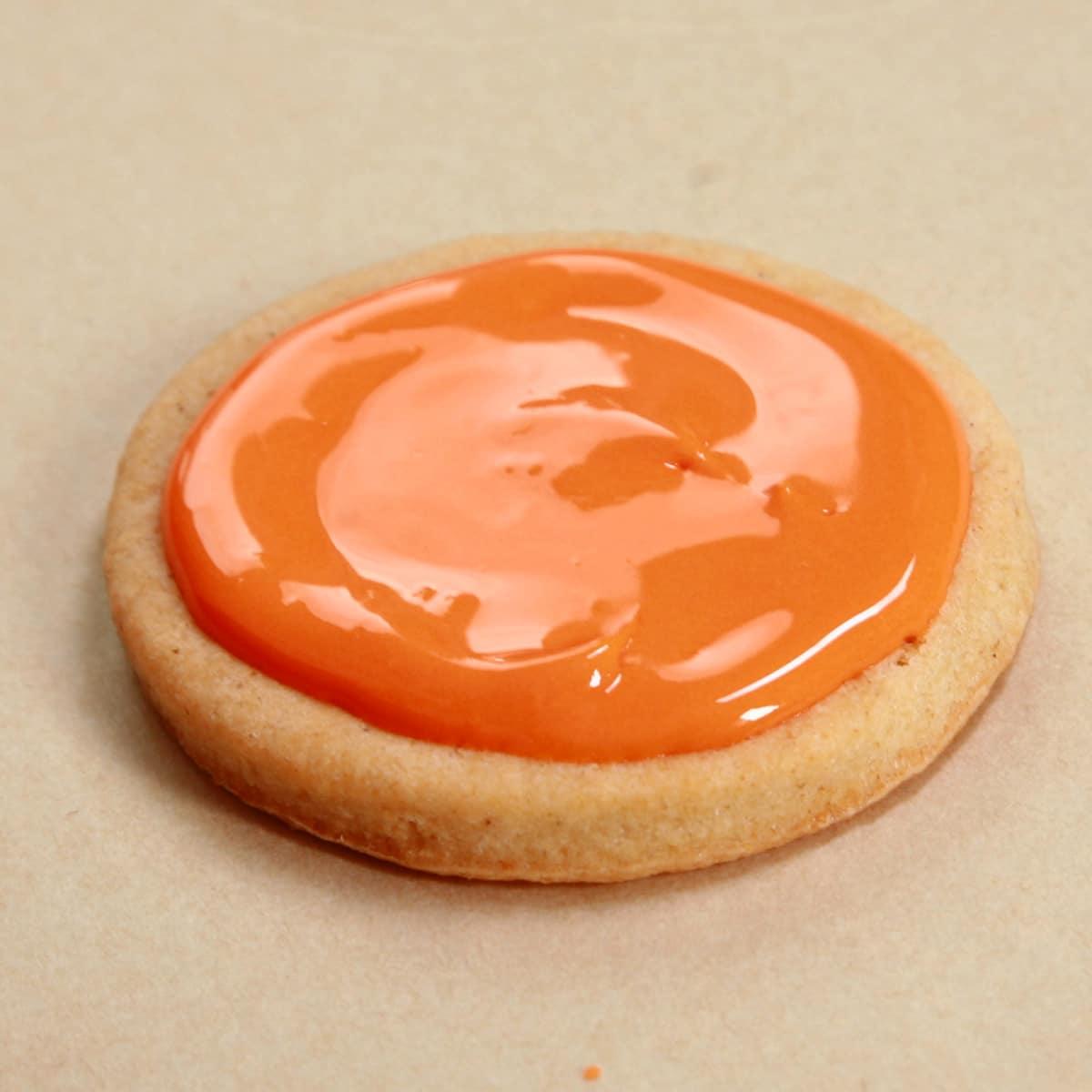 A round sugar cookie, iced with shiny orange glaze.