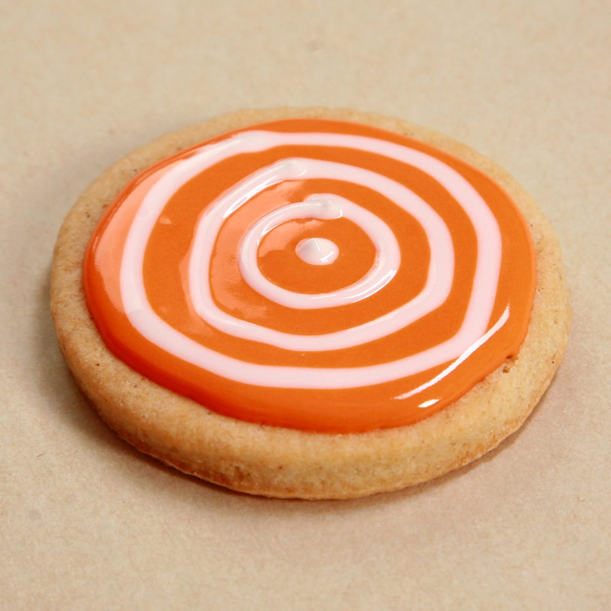 concentric circles of white frosting, piped out on the orange glazed cookie.
