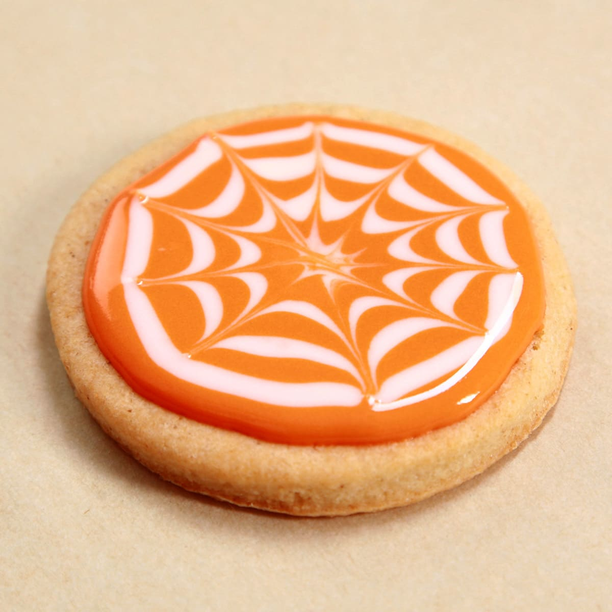 A round sugar cookie frosted orange, with a white spiderweb design.