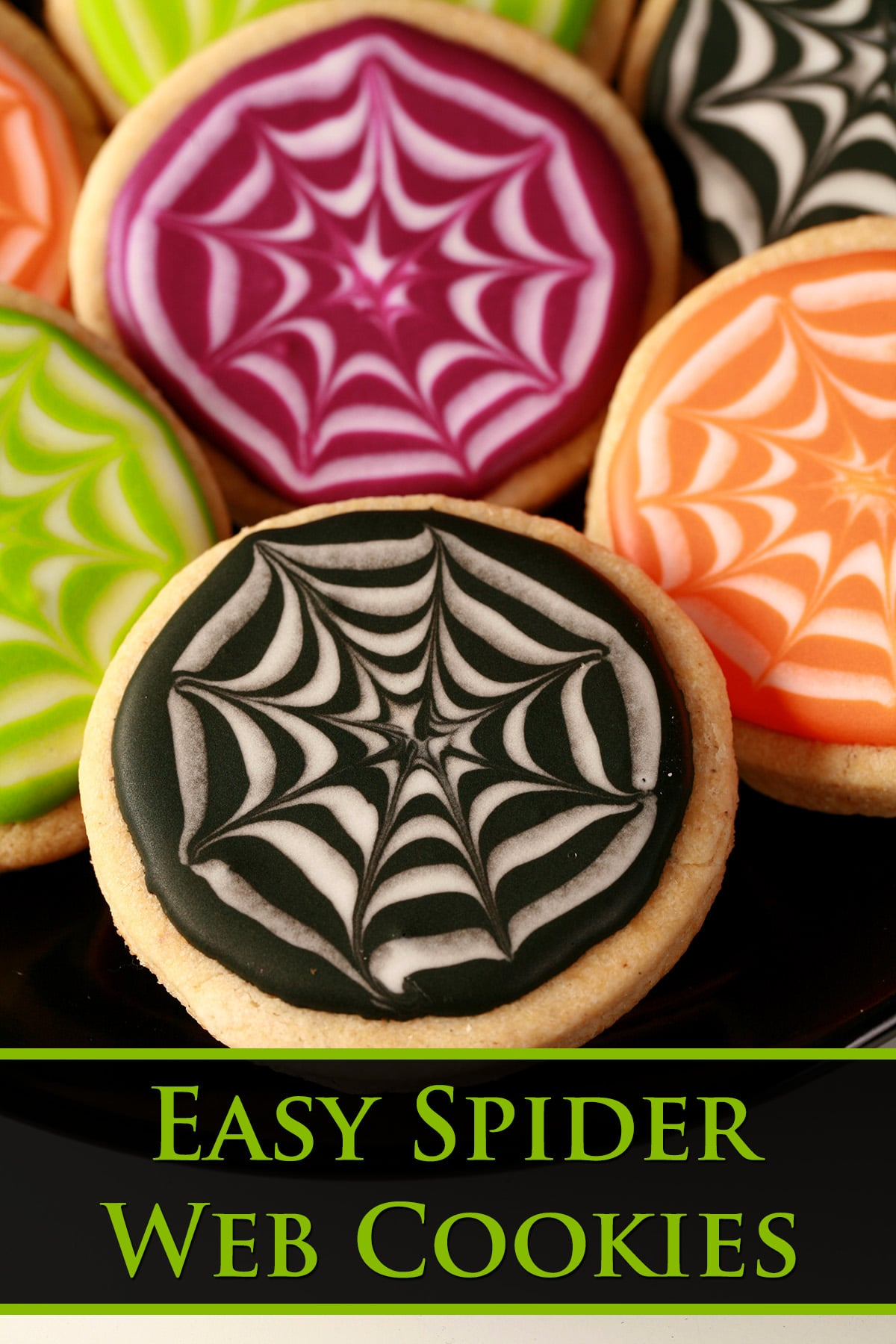 Close up view of a plate of round halloween cookies, frosted with orange, lime green, purple, and black individually. Each has a white stylized spider web design in the coloured background.