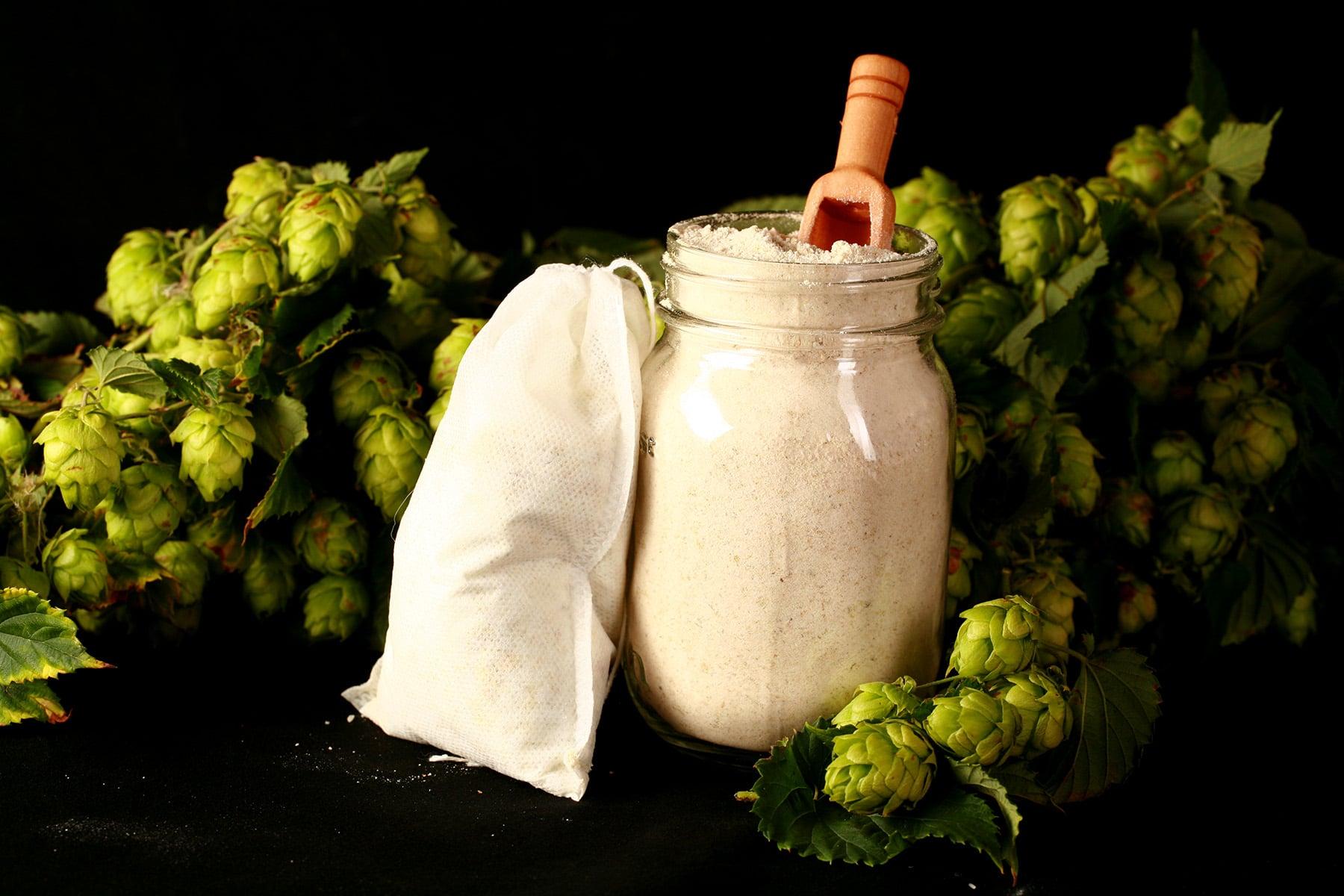 A close up view of a jar - and bath tea bag - of hop malted milk bath.