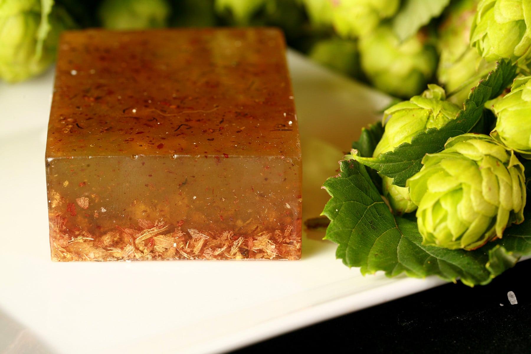A close up photo of a deep amber bar of hop soap.