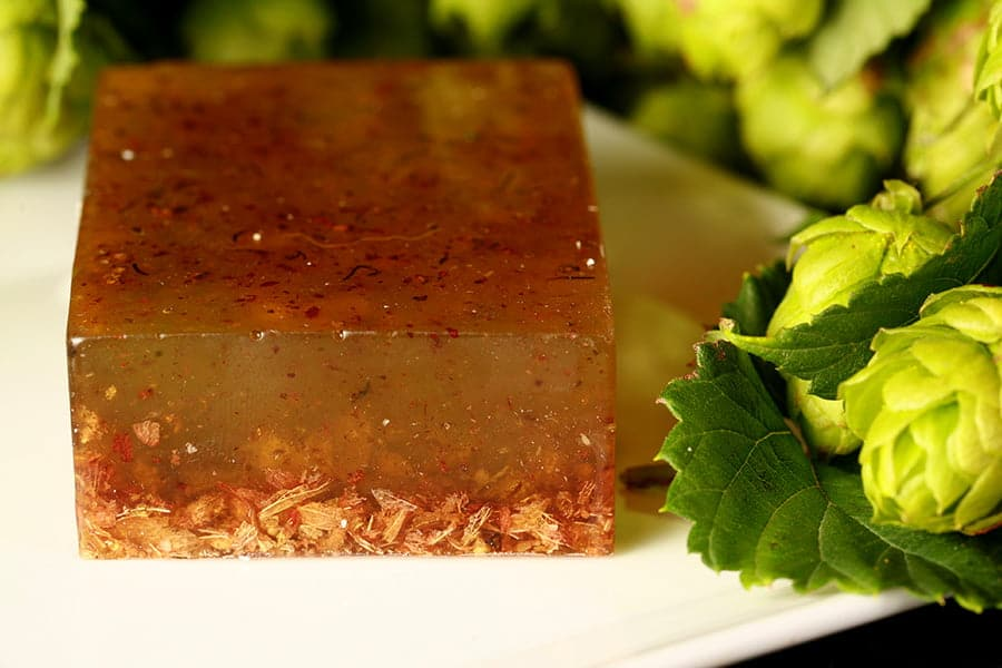 Close up view of a deeply amber coloured bar of soap, with green hops next to it.