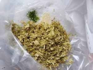 Close up view of a plastic baggie with powders in it, to make Hop Spa products