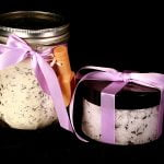 Photo of a set of two jars - one has pale lavender sugar scrub, the other has a milk bath powder. Both are wrapped with lavender coloured satin bows.