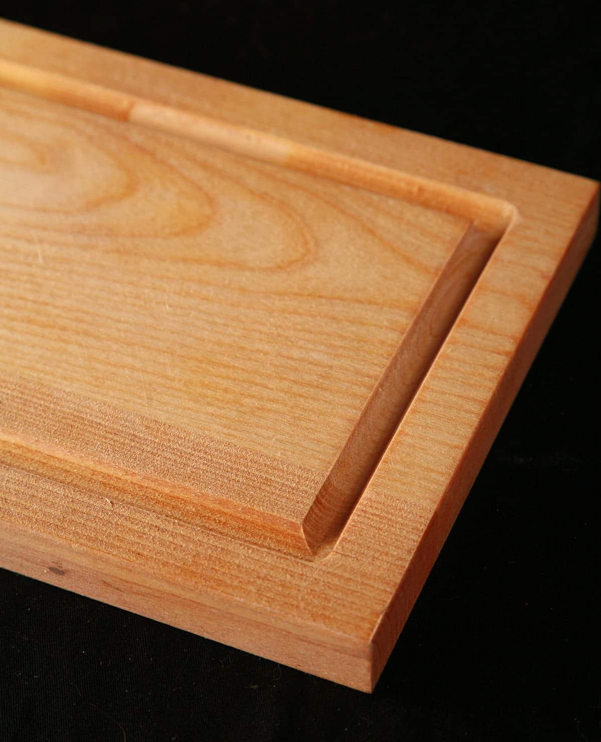 A small wooden cutting board with a groove cut around it.