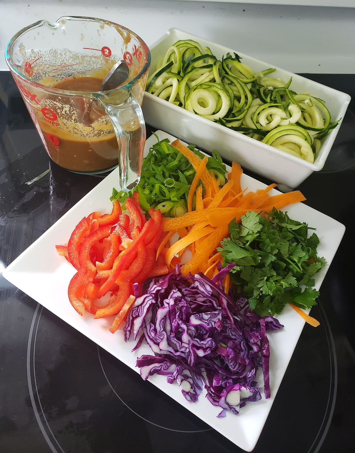A plate of prepared veggies - thinly sliced red pepper and purple cabbage, ribbons of carrots, sliced green onions, and chopped cilantro. In the background is a glass measuring cup full of peanut sauce, and a tray with spiralized zucchini in it.