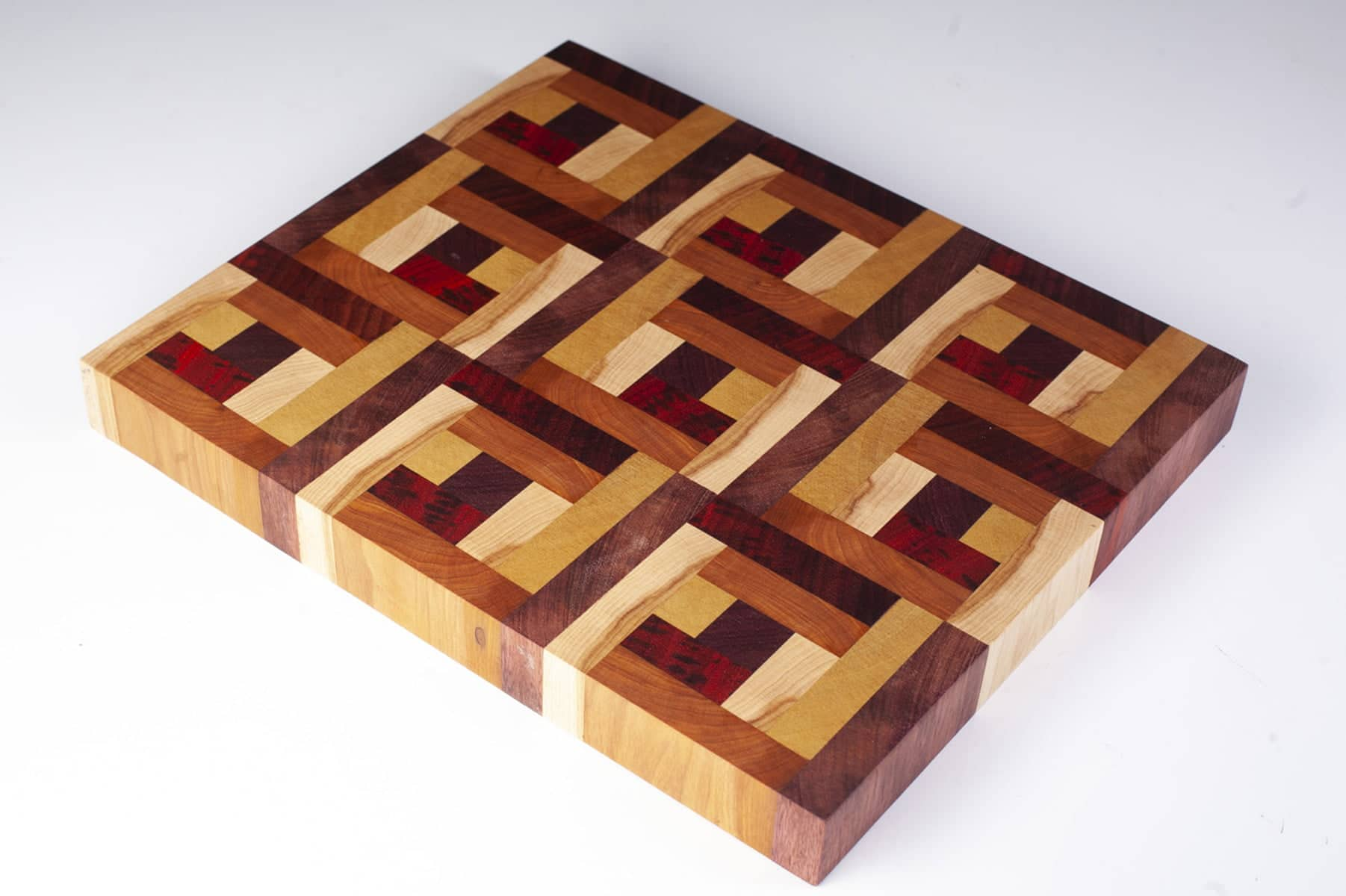 Close up image of a fancy cutting board made of many small pieces of multicoloured wood.