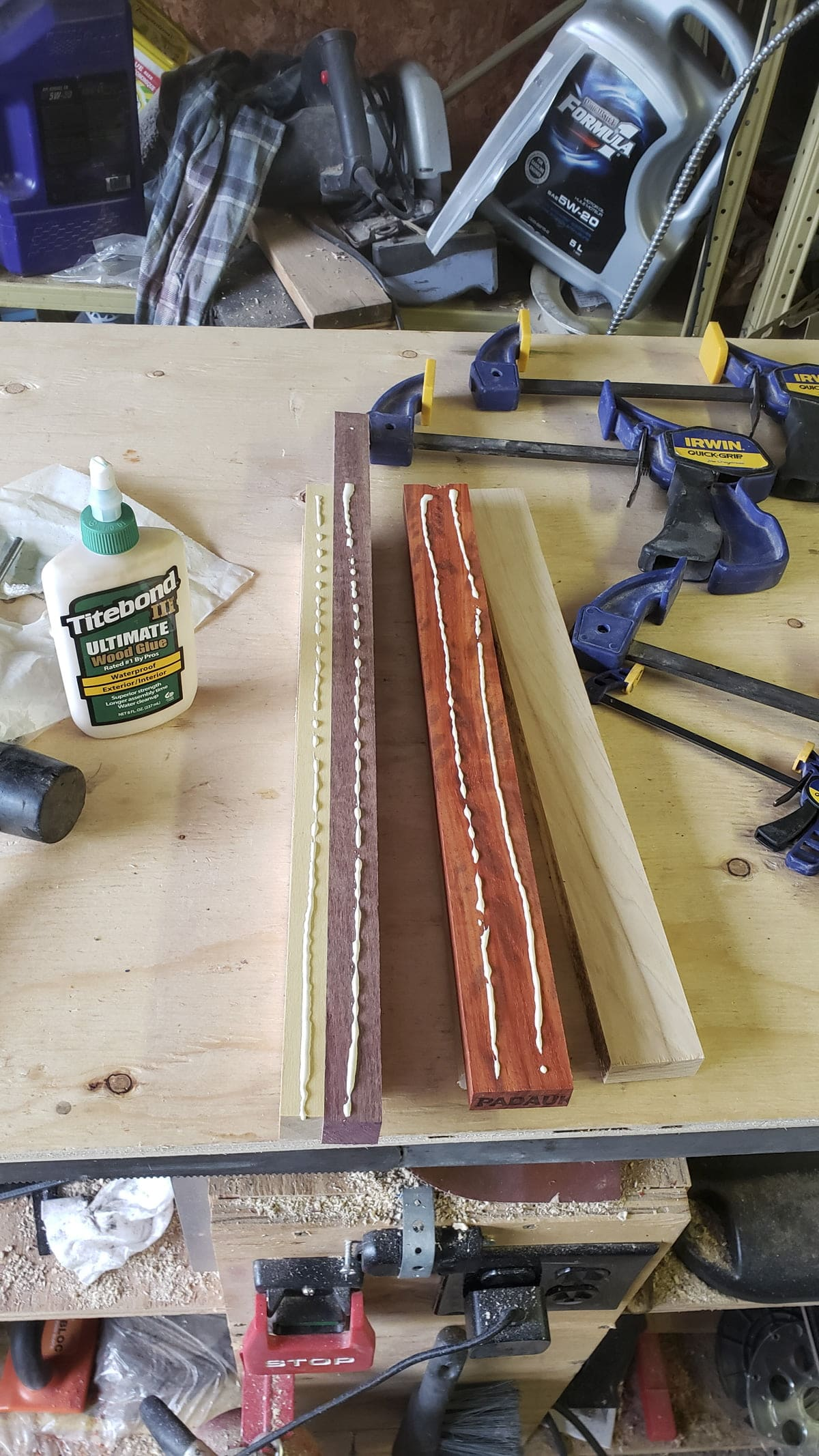 Two strips of different colored wood are on the surface of a table. Lines of glue has been applied to the tops of the wood.