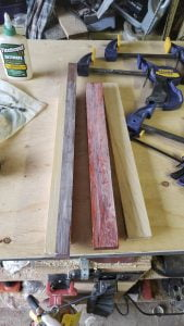 Several strips of different colored wood are on the surface of a table. A thin coat of glue has been spread on the top surfaces of the boards.