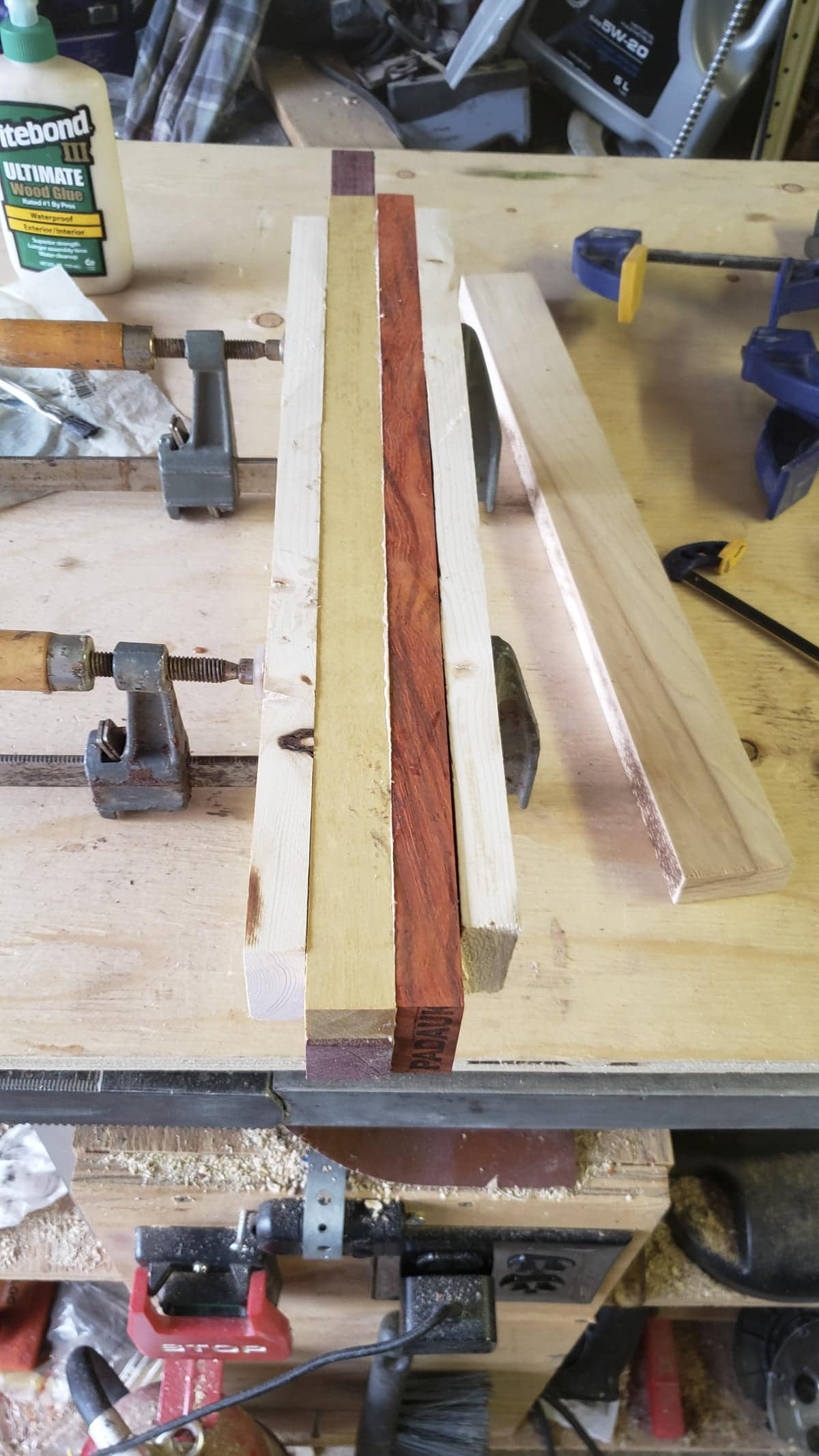 Several small strips of multi-colored wood are held together with two clamps from the bottom.