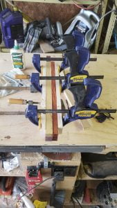 Several small strips of multi-colored wood are held together with five clamps.