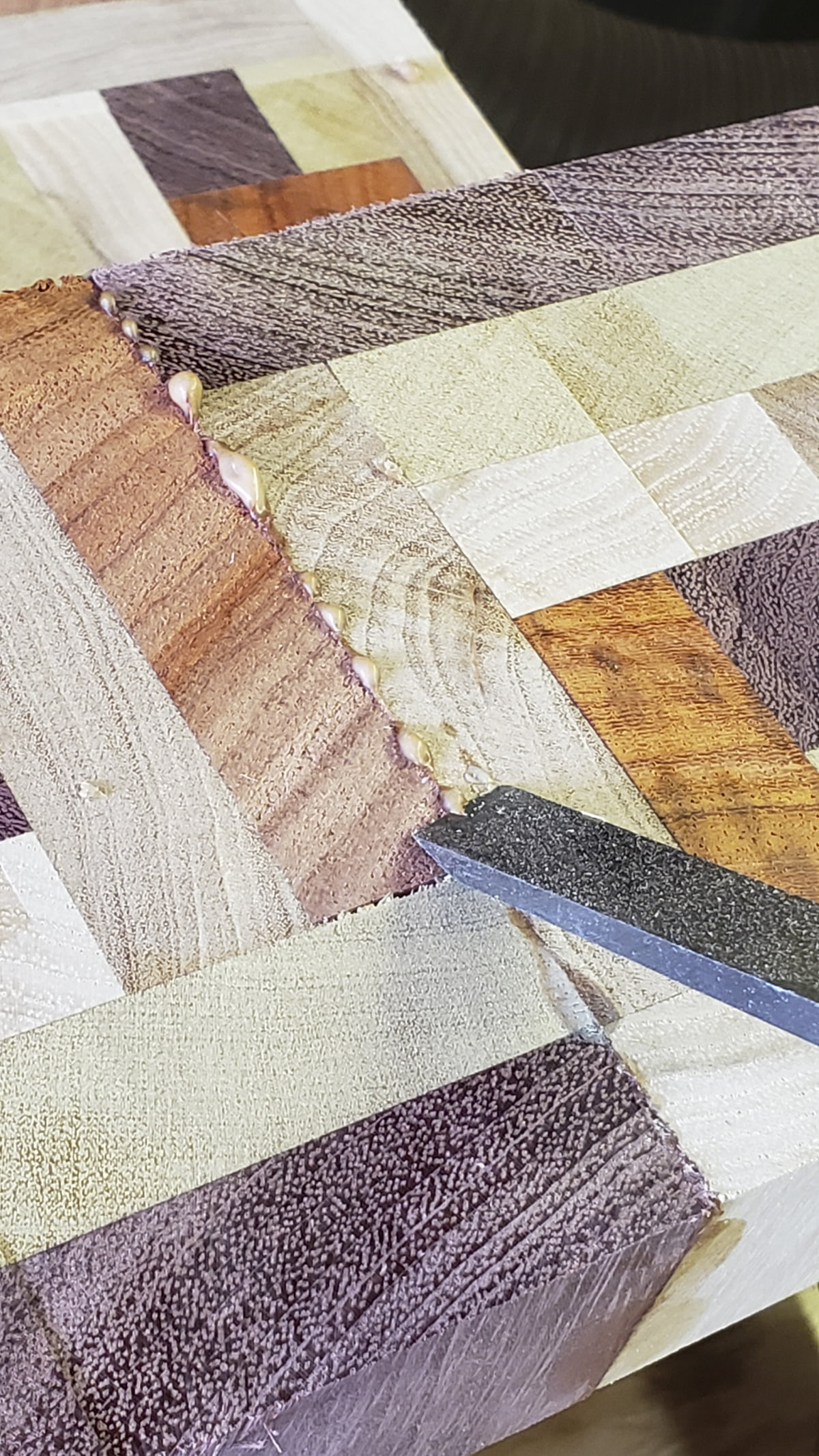 An array of small multi-colored pieces of wood are seen as a flat surface. Glue has bulged out of the seam between two boards. A chisel is on top. The chisel has removed some of the excess glue.