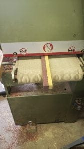 A board made from two smaller strips of different colored woo, purple and yellow, are seen entering a large sanding machine on a conveyor belt.