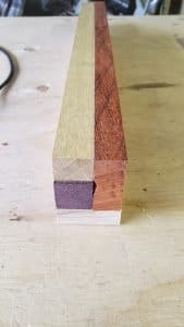 End view of a rectangular board made from several pieces of different colored wood strips.