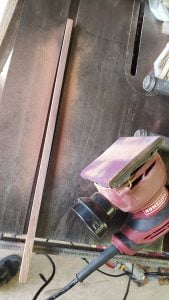 A metal table saw surface has a small strip of wood on it, along with a palm sander. Sawdust is scattered on the table top.