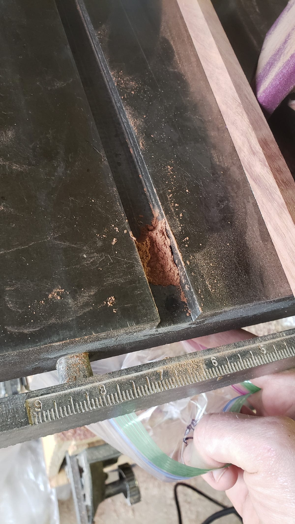 A metal table saw work surface is seen, with a slot. Some wood dust is gathered into the slot.
