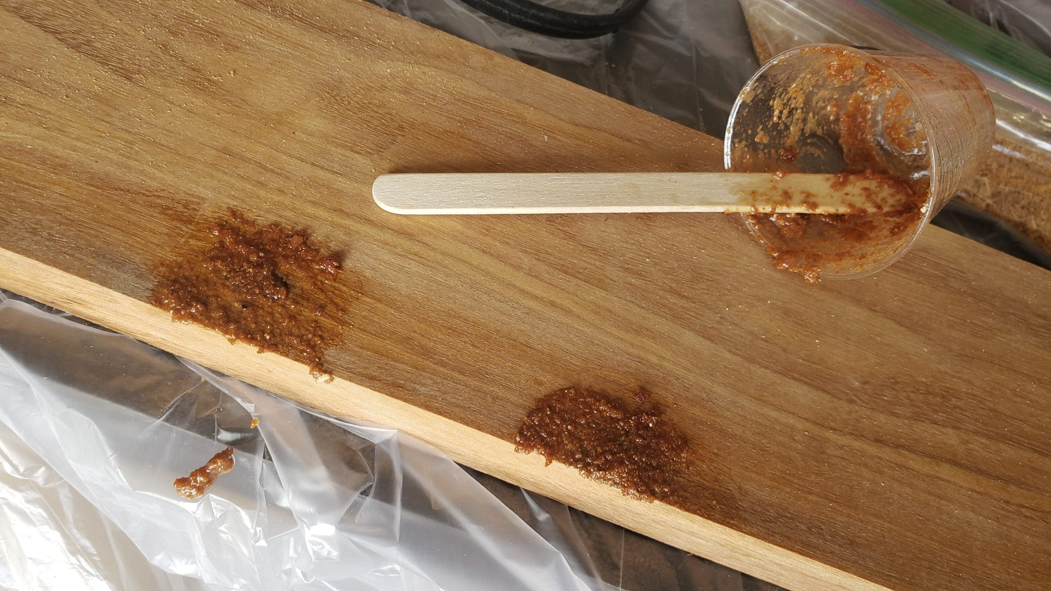 An orange-colored piece of wood is flat on a table. Small sections have a slightly darker colored, thick paste on the surface. A small cup, a craft stick, and more of the dark epoxy are seen nearby.