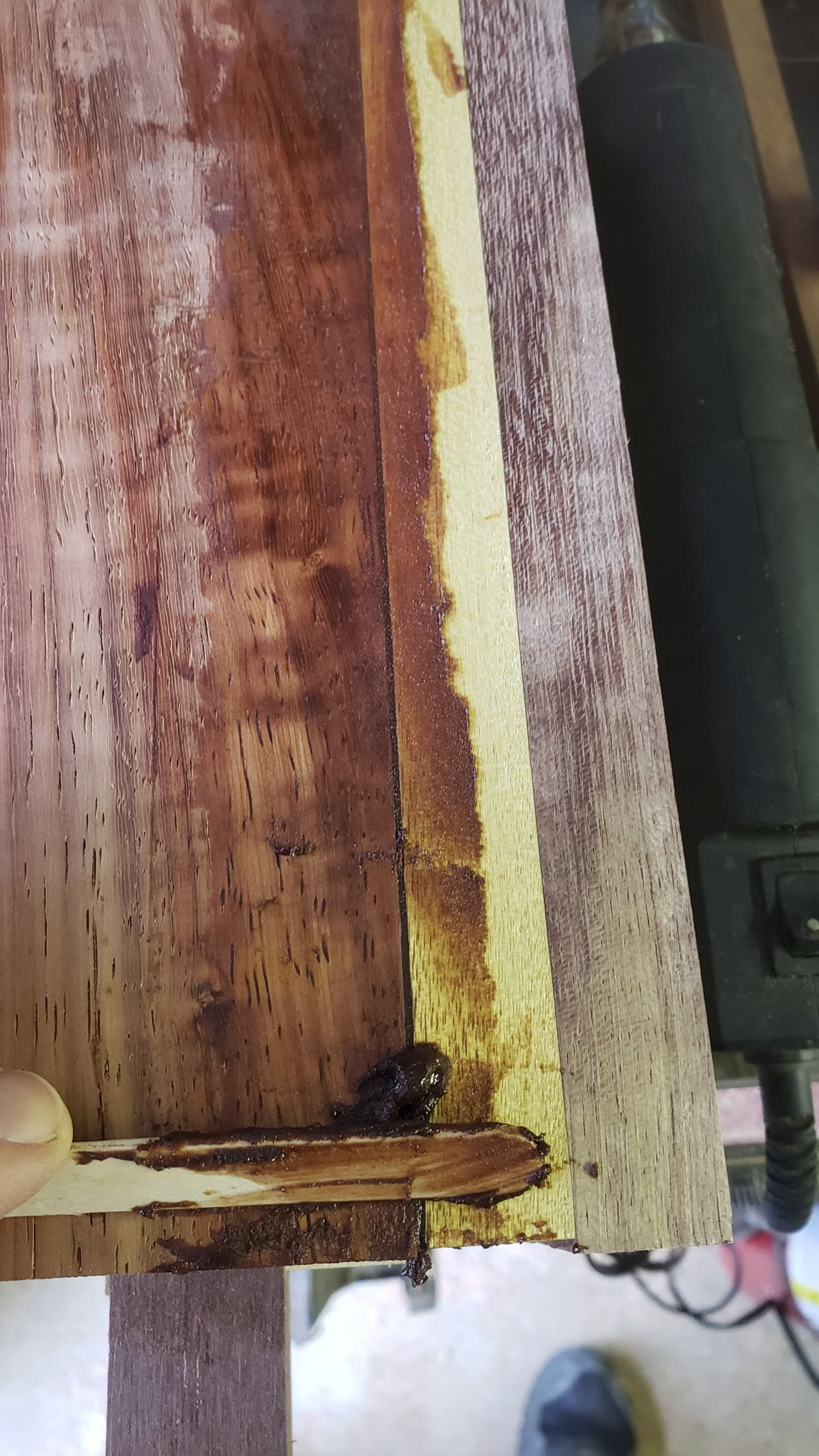 Two boards with a small gap are seen on a table. Dark epoxy has been pressed into the crack, and is seen smeared along the surface. A popsicle stick at an angle is seen plowing the adhesive into the crack.