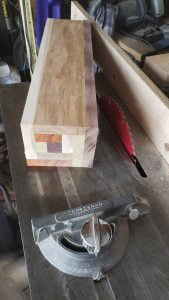 A rectangular block, made from several smaller pieces of different colored wood, is on top of a table saw.
