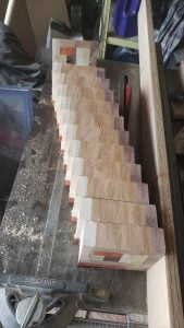A rectangular block of wood has been sliced into eleven segments of equal size. The segments are spread slightly. The segments are arranged on top of a table saw.