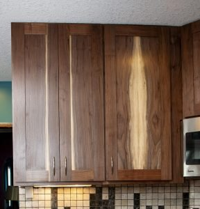 Two upper kitchen cabinets made from dark wood. Lighter sections of the wood are seen in the center of the doors. The natural grain of the wood is seen symmetrically outward from the center.