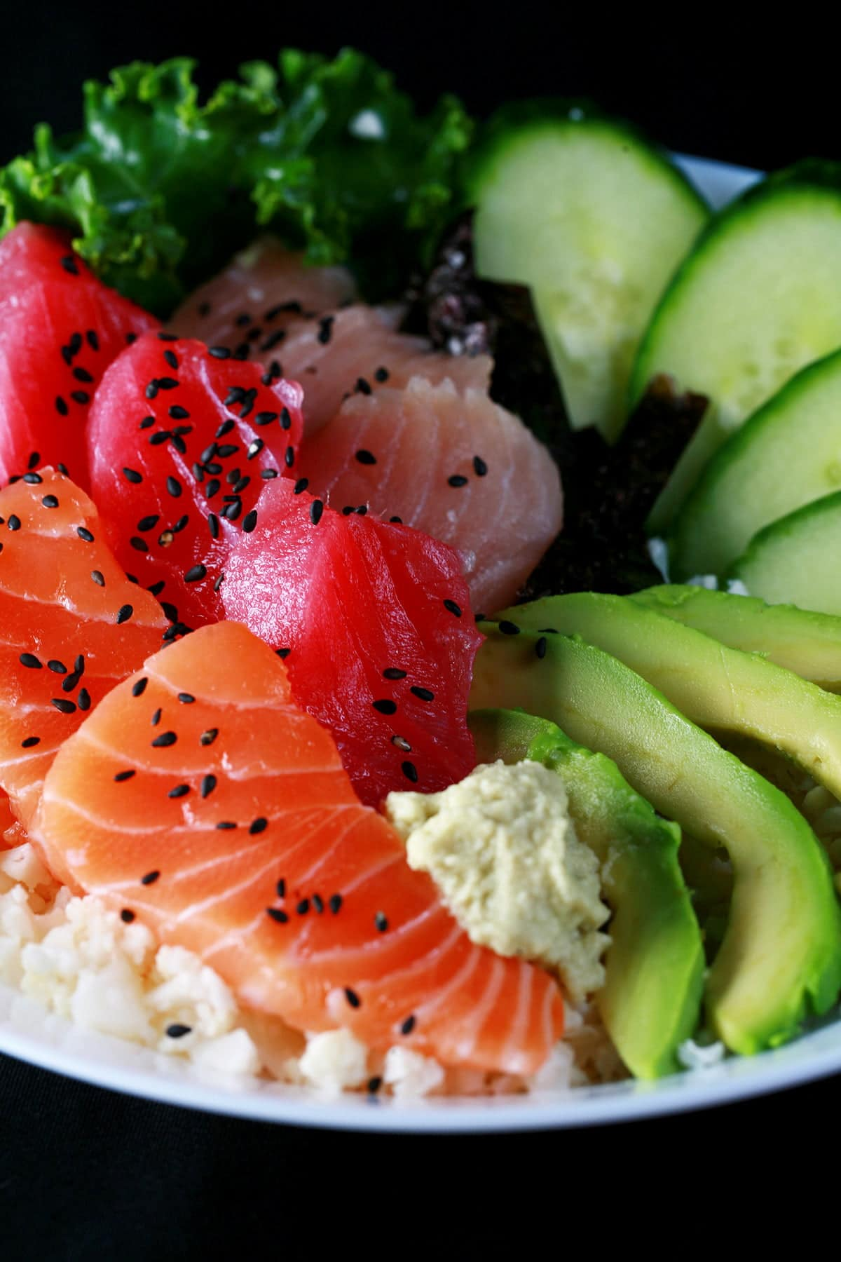 A low carb chirashi bowl - A shallow bowl with various cuts of fish - salmon, tuna, and snapper - as well as some veggies.  It is all arranged on top of riced cauliflower.