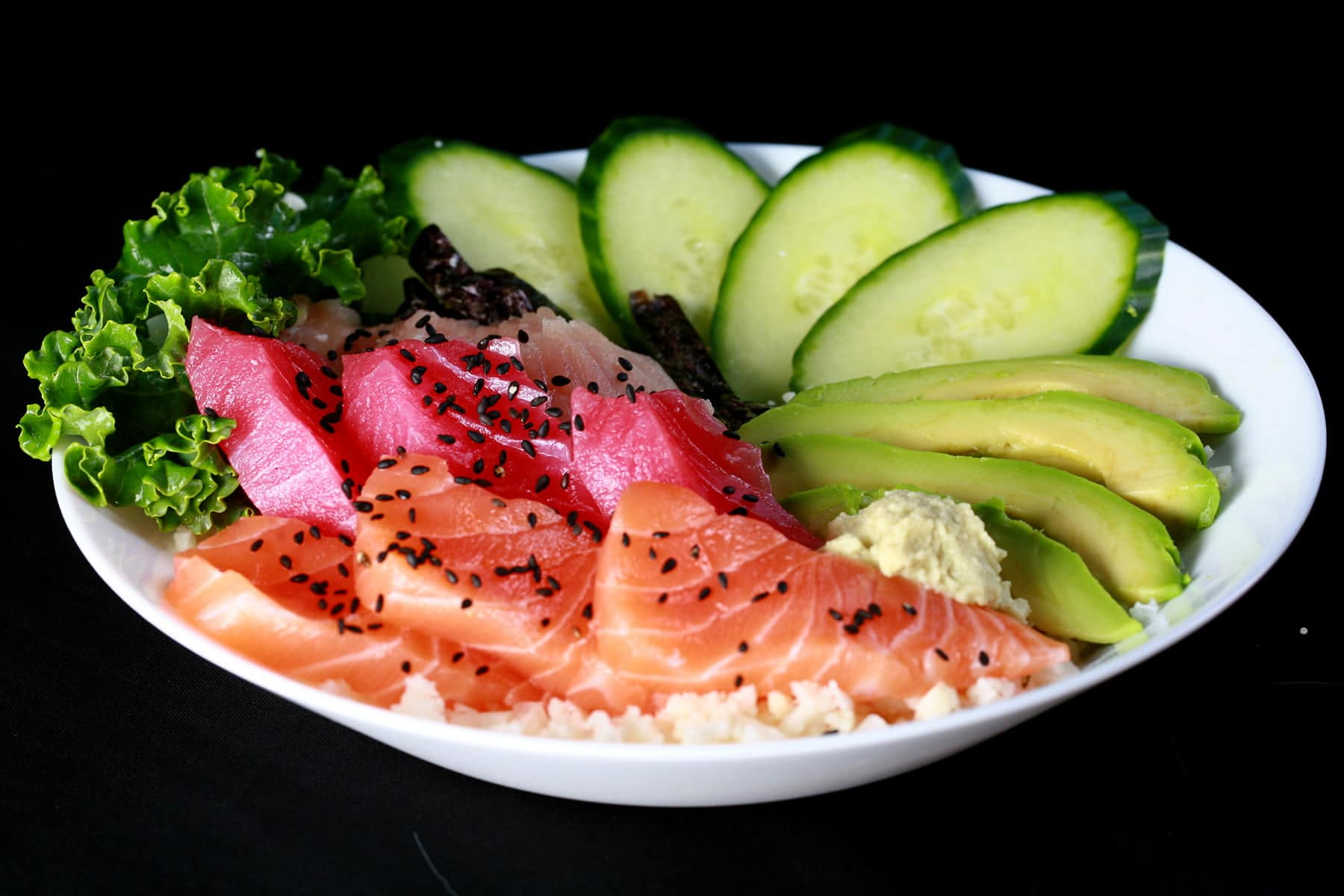 A shallow bowl with various cuts of fish - salmon, tuna, and snapper - as well as some veggies.  It is all arranged on top of riced cauliflower.