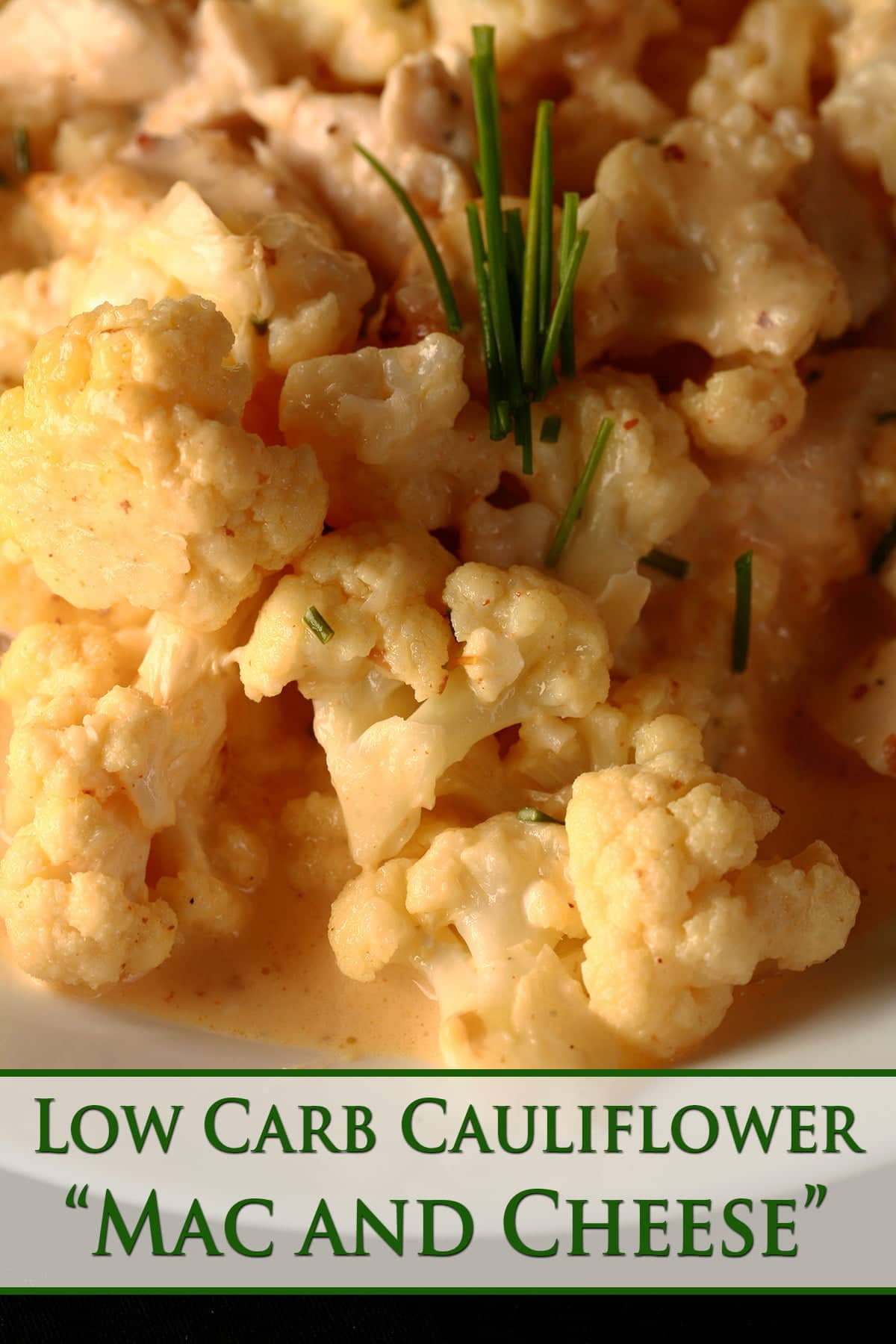 Close up view of a bowl of small pieces of cauliflower, coated in a creamy cheese sauce.
