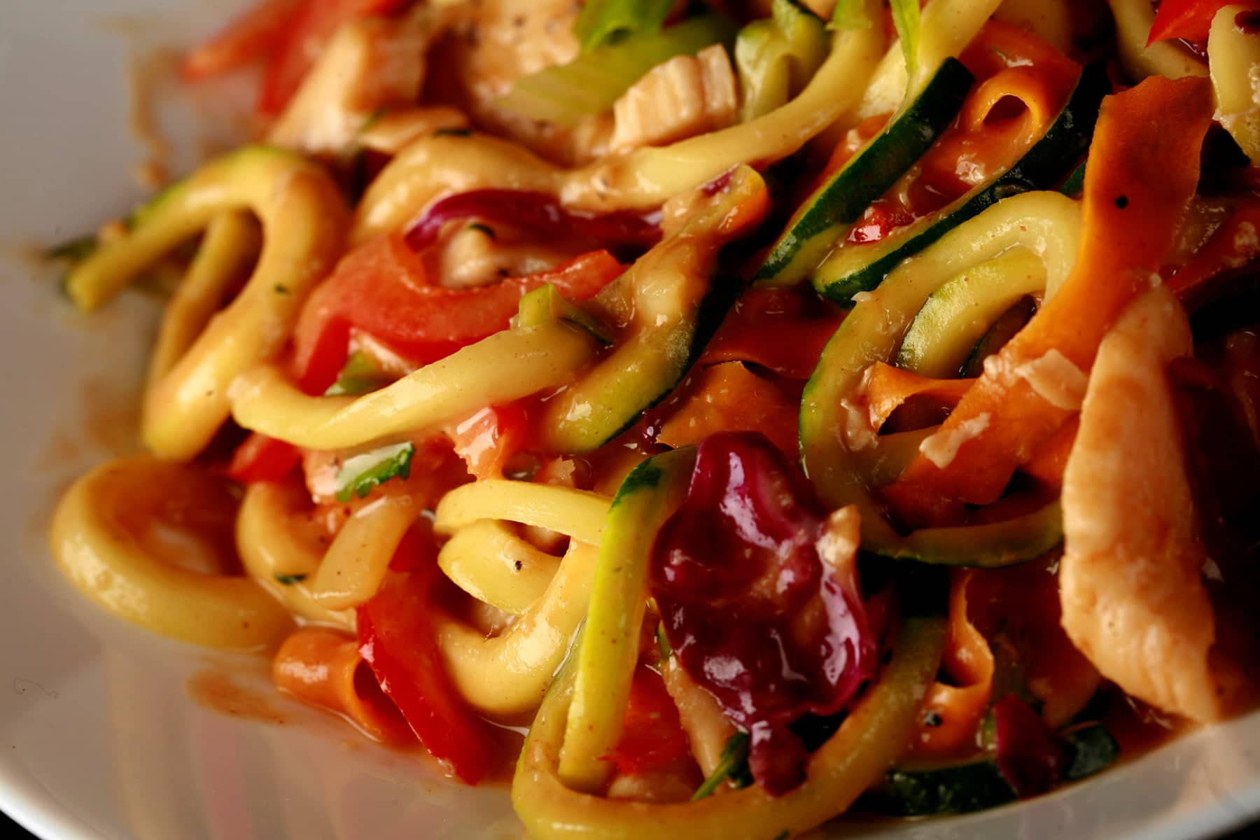 "A close up view of a colourful ""zoodles"" dish - zucchini noodles, purple cabbage, carrot strups, thinly sliced red pepper, green onions, and cilantro, in a translucent peanut sauce."