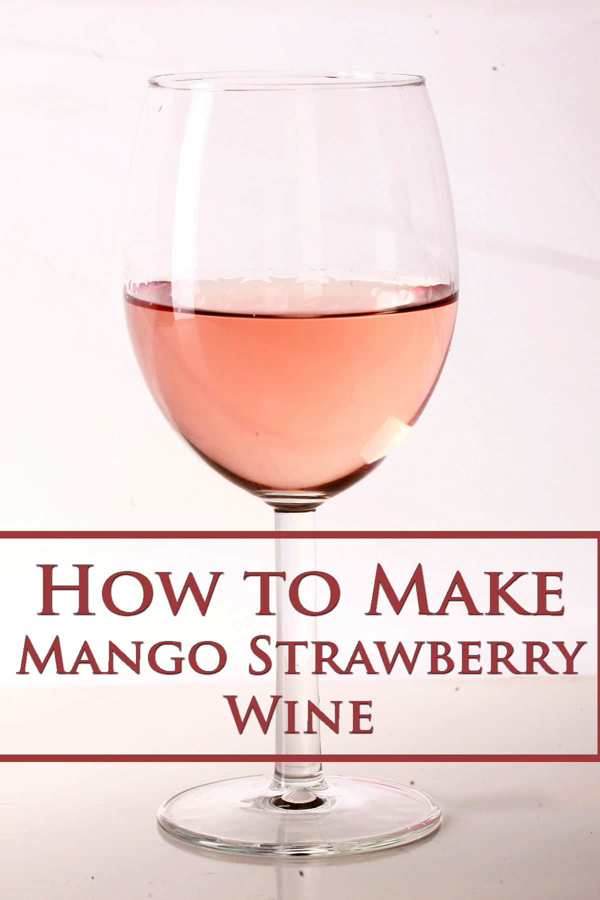 """A close up view of a glass of pink wine, labelled with """"How to make mango strawberry wine"""""""