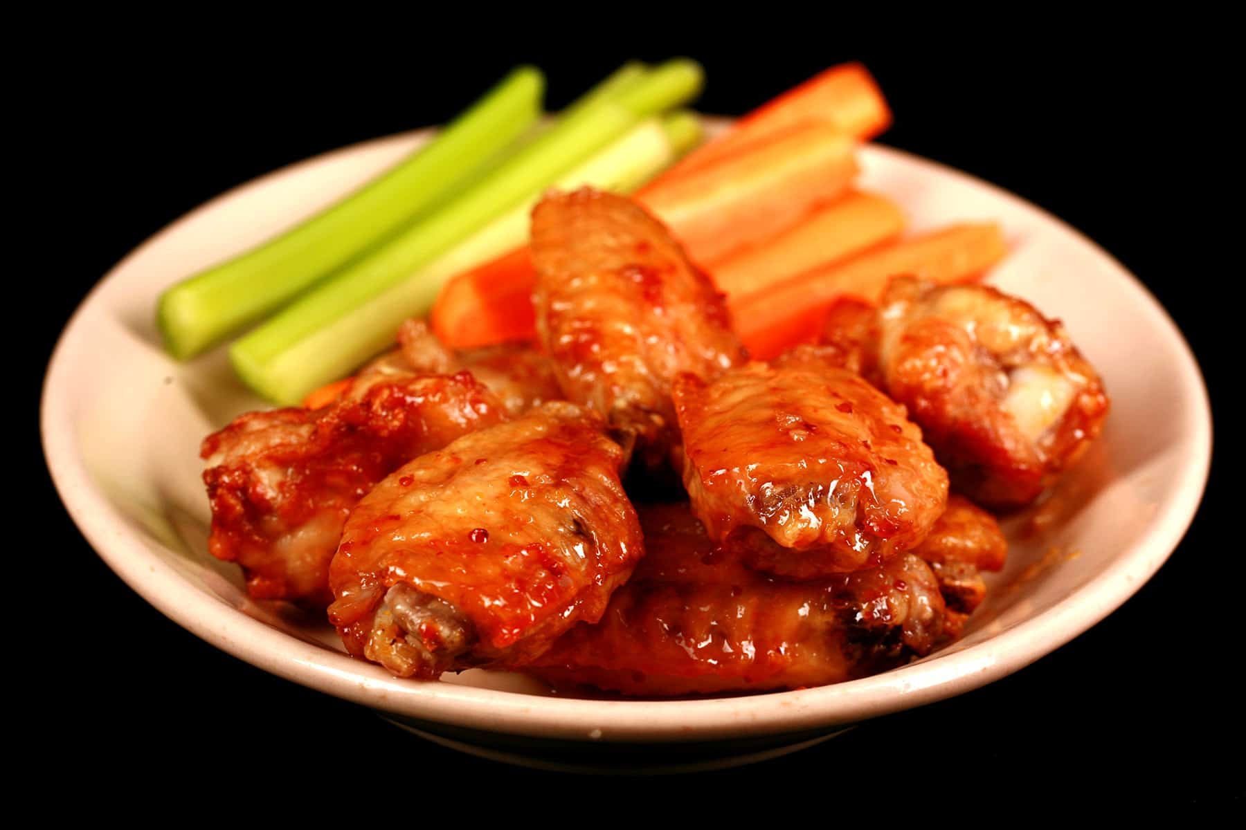A small plate of maple dijon wings, with carrot and celery sticks on the side.