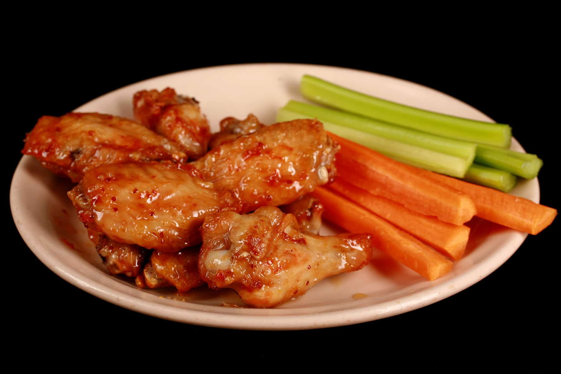 A small plate of maple dijon glazed wings, with carrot and celery sticks on the side.