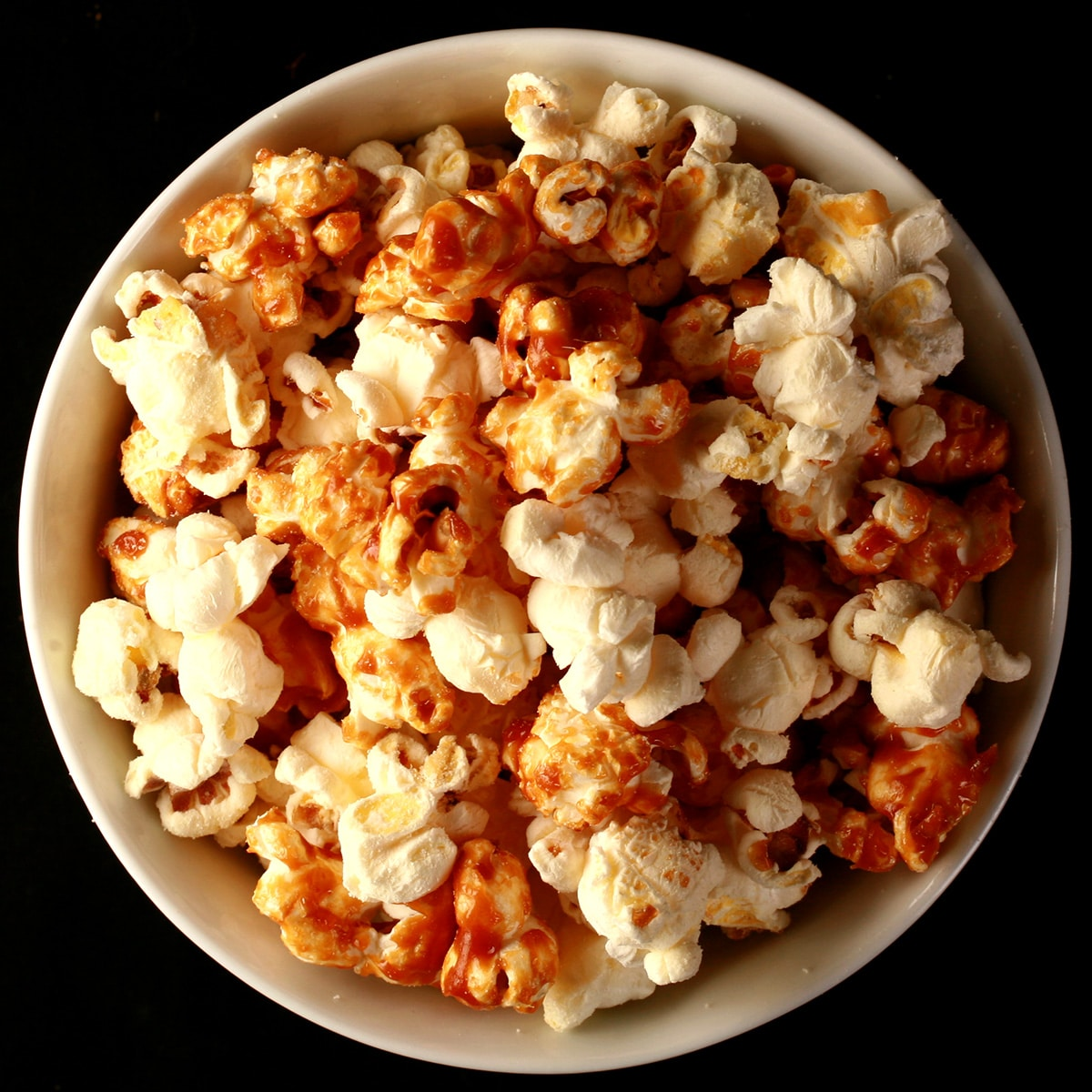 Close up photo of a bowl of two-tone popcorn: Maple White Cheddar Popcorn. Half of the popcorn is covered with maple caramel, the other half is white - white cheddar.