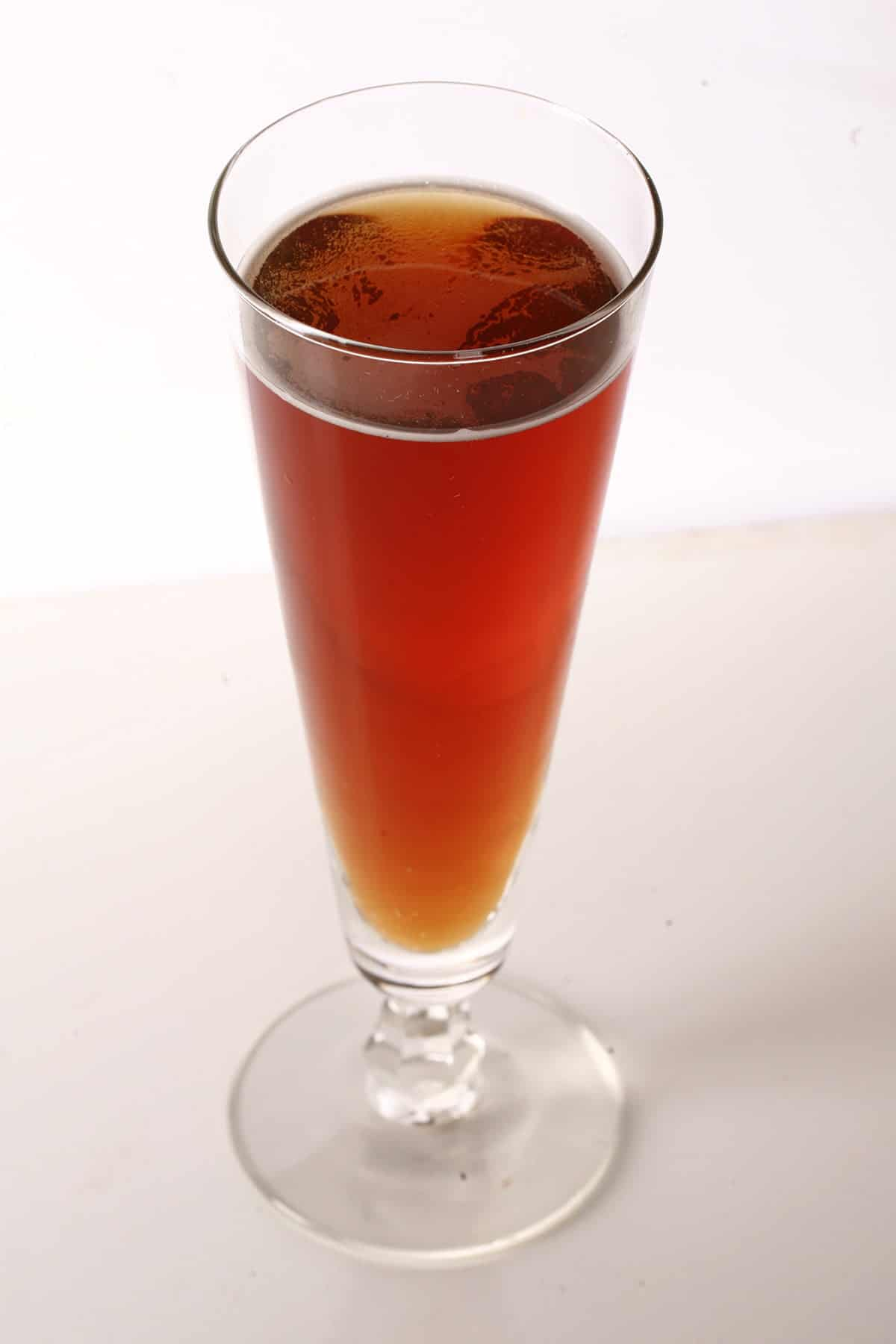 Photo of a tall glass of deep amber apple cider - Maple Hard Apple Cider.