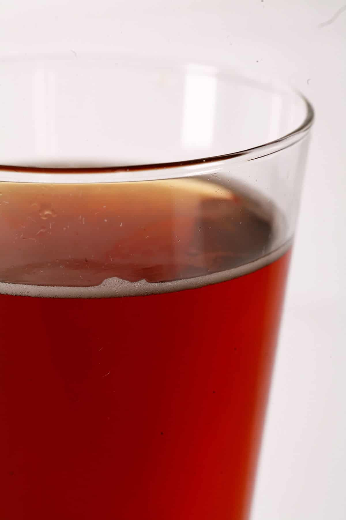 Photo of a tall glass of deep amber apple cider.
