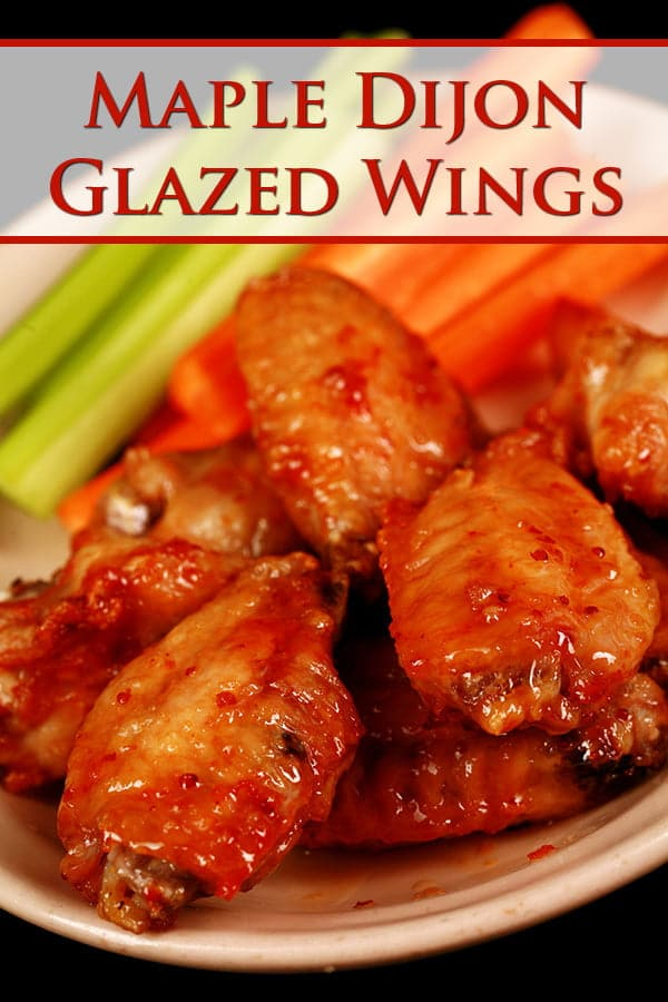 Close up photo of a plate of glazed chicken wings. There are celery and carrot sticks on the plate as well.