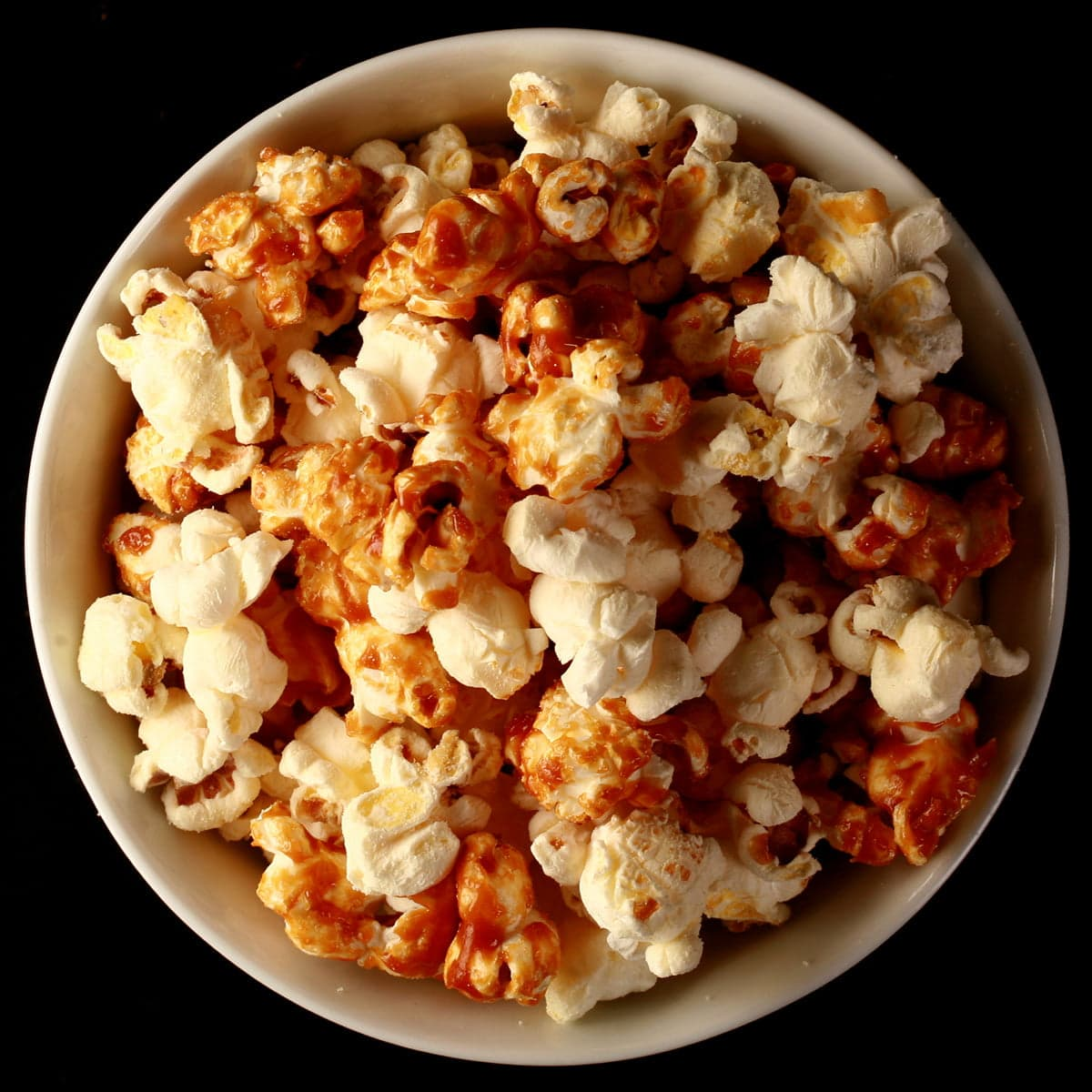 Close up photo of a bowl of two-tone popcorn: Maple White Cheddarl Popcorn. Half of the popcorn is covered with maple caramel, the other half is white - white cheddar.