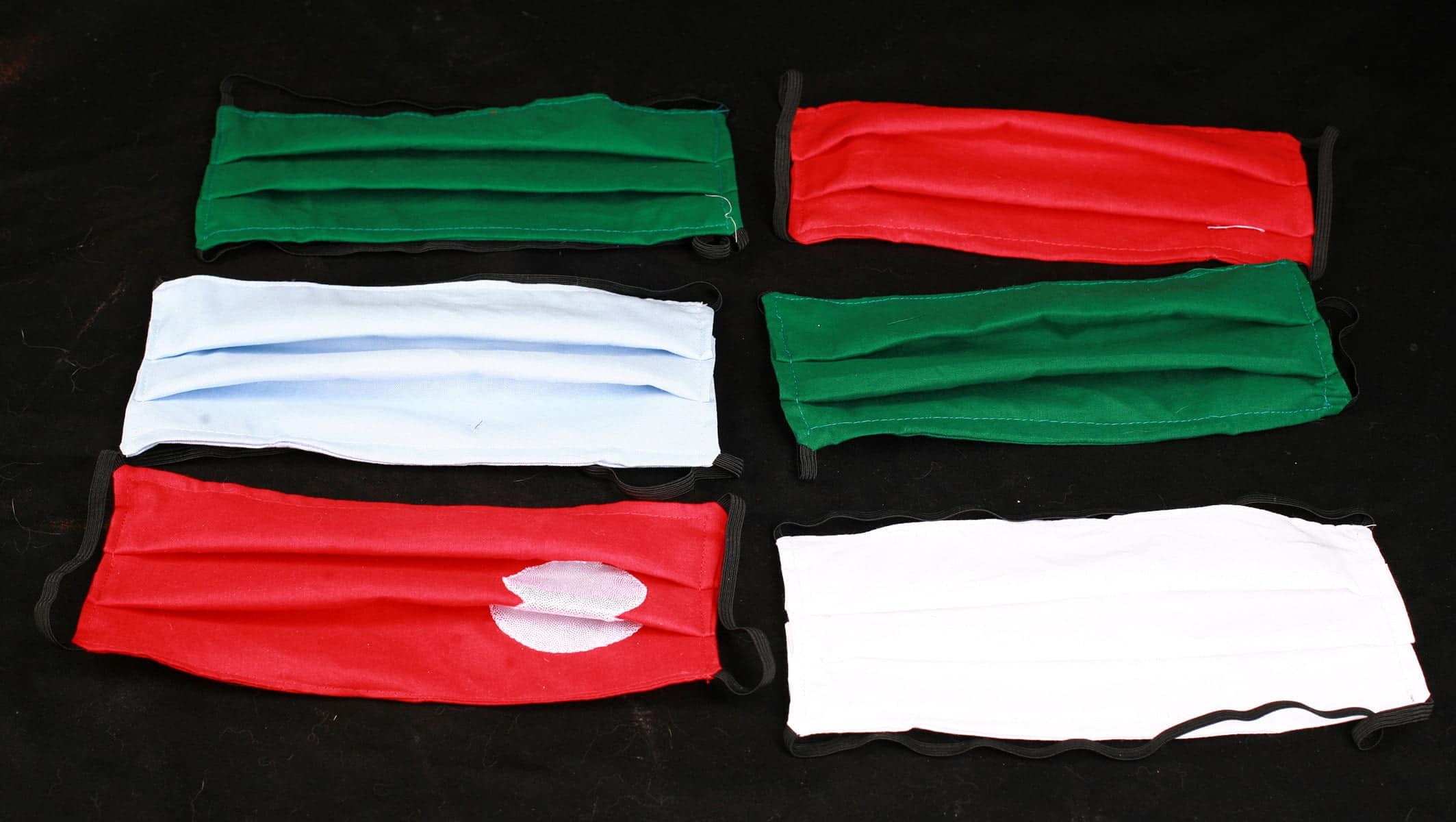 A selection of face masks in Holiday colours - 2 green, 2 red, 1 white, 1 light blue.