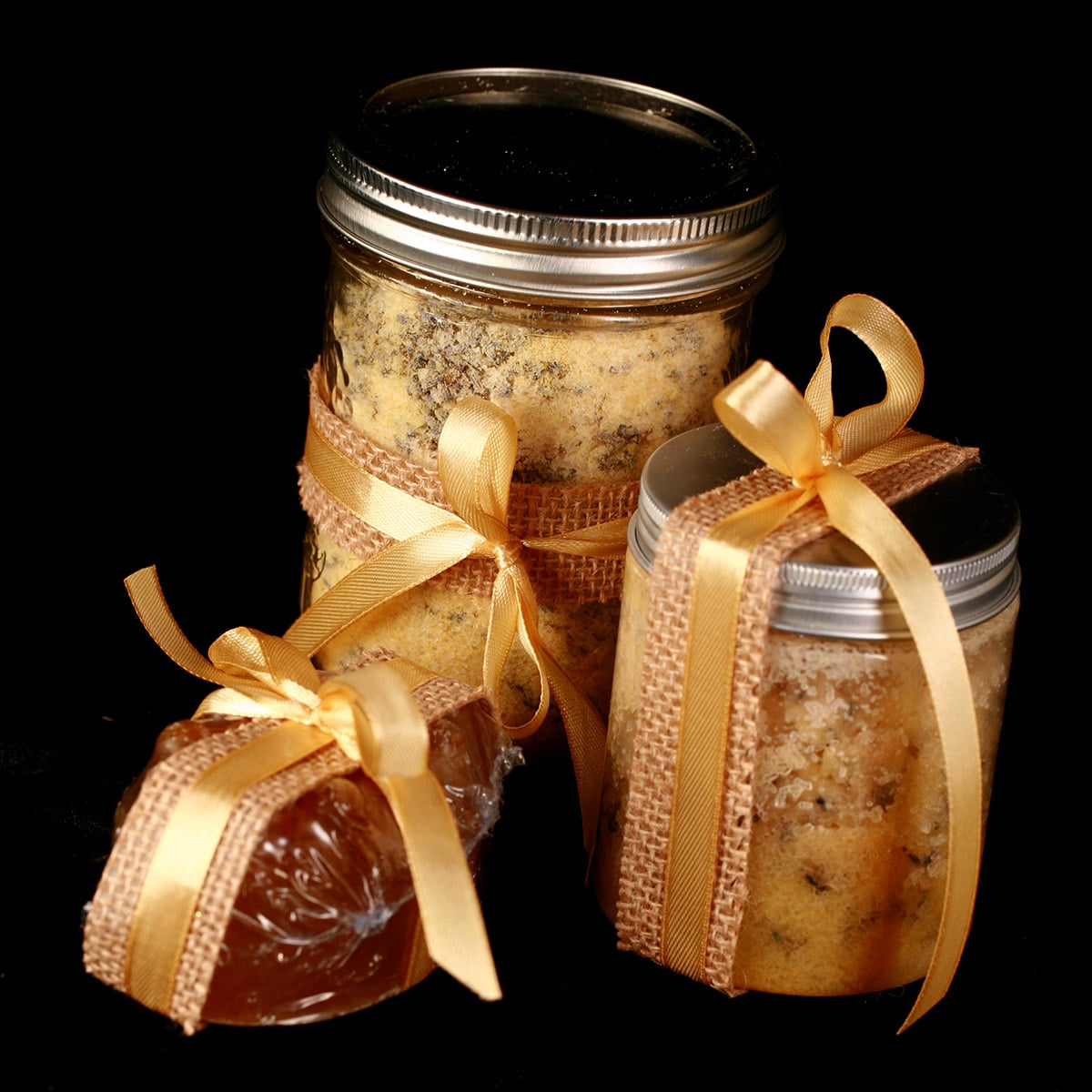 A 3 piece mustard bath gift set - the mustard bath salt, a salt scrub, and a nubby yellow mustard soap. They are all accented with yellow ribbon.