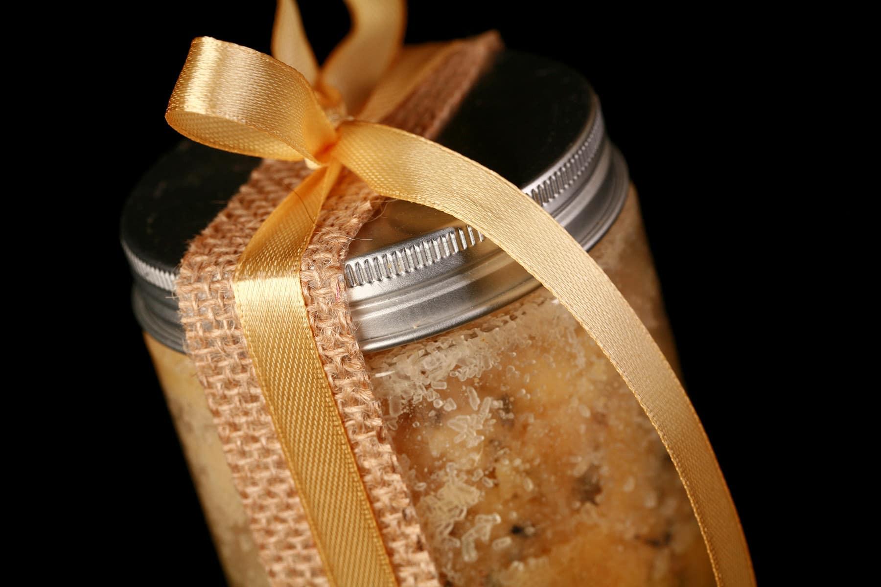 A small jar of mustard bath salt scrub. It is tied with a yellow bow.