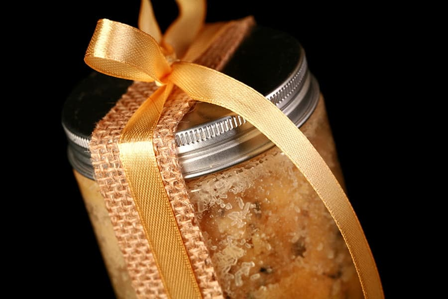 Close up view of a small jar filled with yellow salts and a small wooden scoop, It is tied up with a yellow bow.