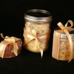 3 bath items, all wrapped with yellow bows. One is a clear bar of yellow soap, next to a jar of yellow bath salts. Finally, there is a smaller jar of yellow coloured scrub.