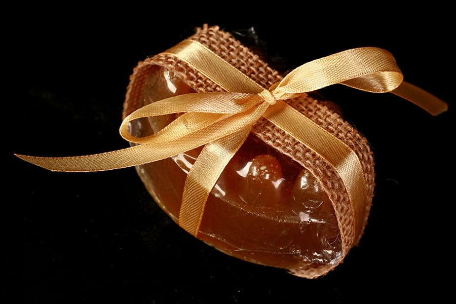 Close up view of a deep orange-yellow bar of soap, wrapped with ribbon