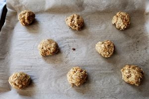 A sheet pan, lined with parchment paper, with balls of cookie dough arranged on it.