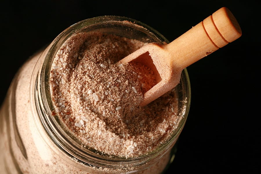 Close up photo of a mason jar filled with light brown bath salt. There is a small wooden scoop on top.alt