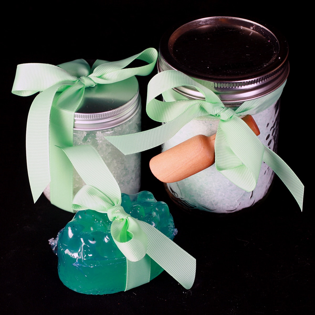 A three piece peppermint-eucalyptus bath set - bath salt, salt scrub, and a soap. Each is wrapped with a light green bow.