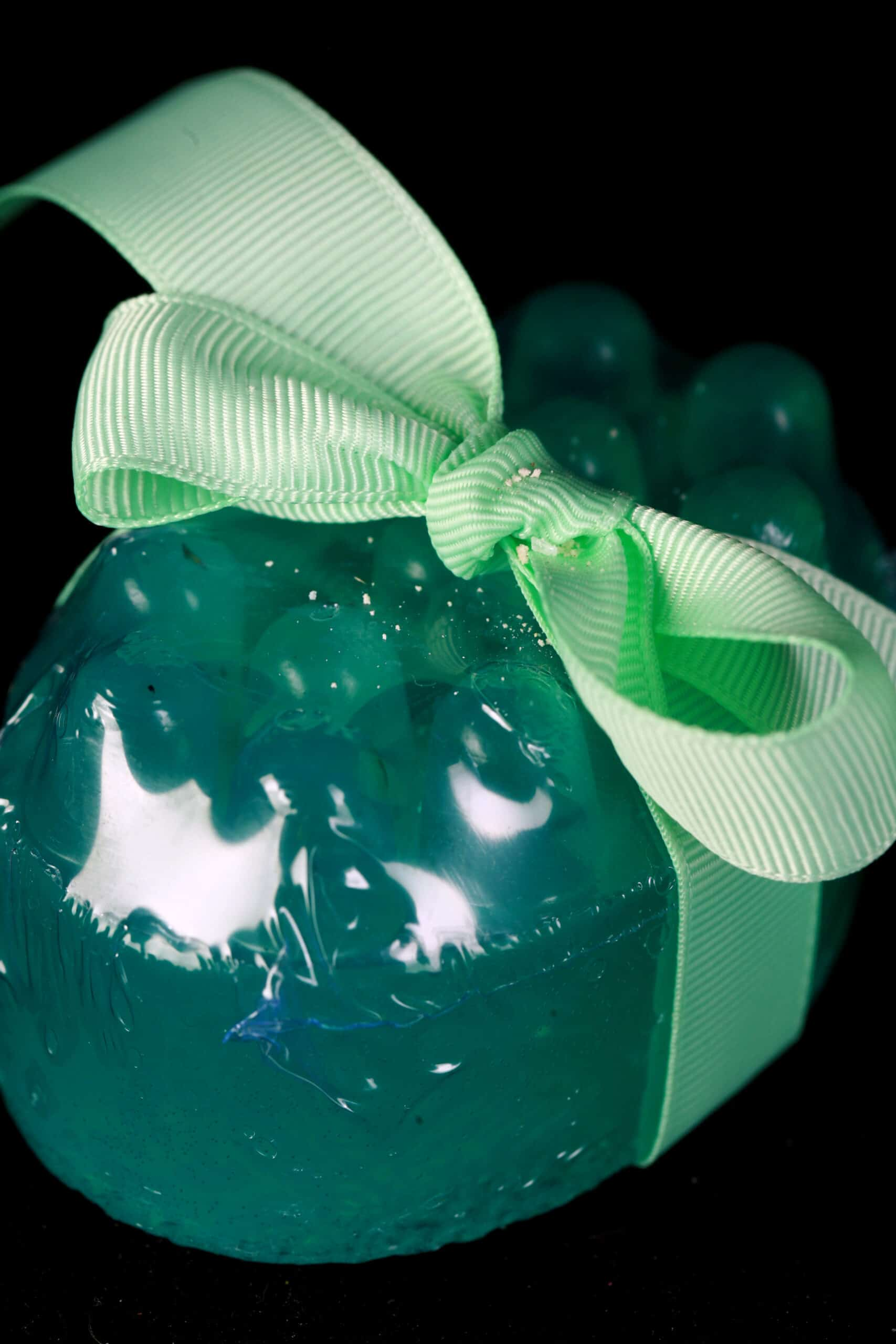 A small, blue-green nubby bar of peppermint eucalyptus soap, tied with a light green bow.