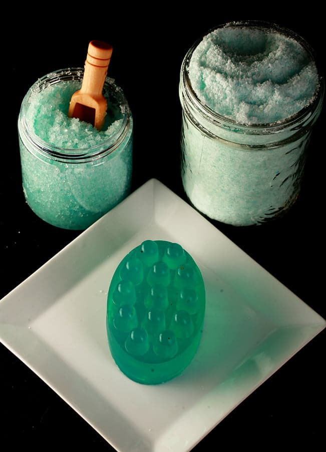Close up photo of a set of 3 homemade peppermint-eucalyptus bath products. There is a bright blue-green oval bar of soap with nubs on top, a small just of a wet looking blue-green salt, and a larger mason jar filled with light blue-green salt.