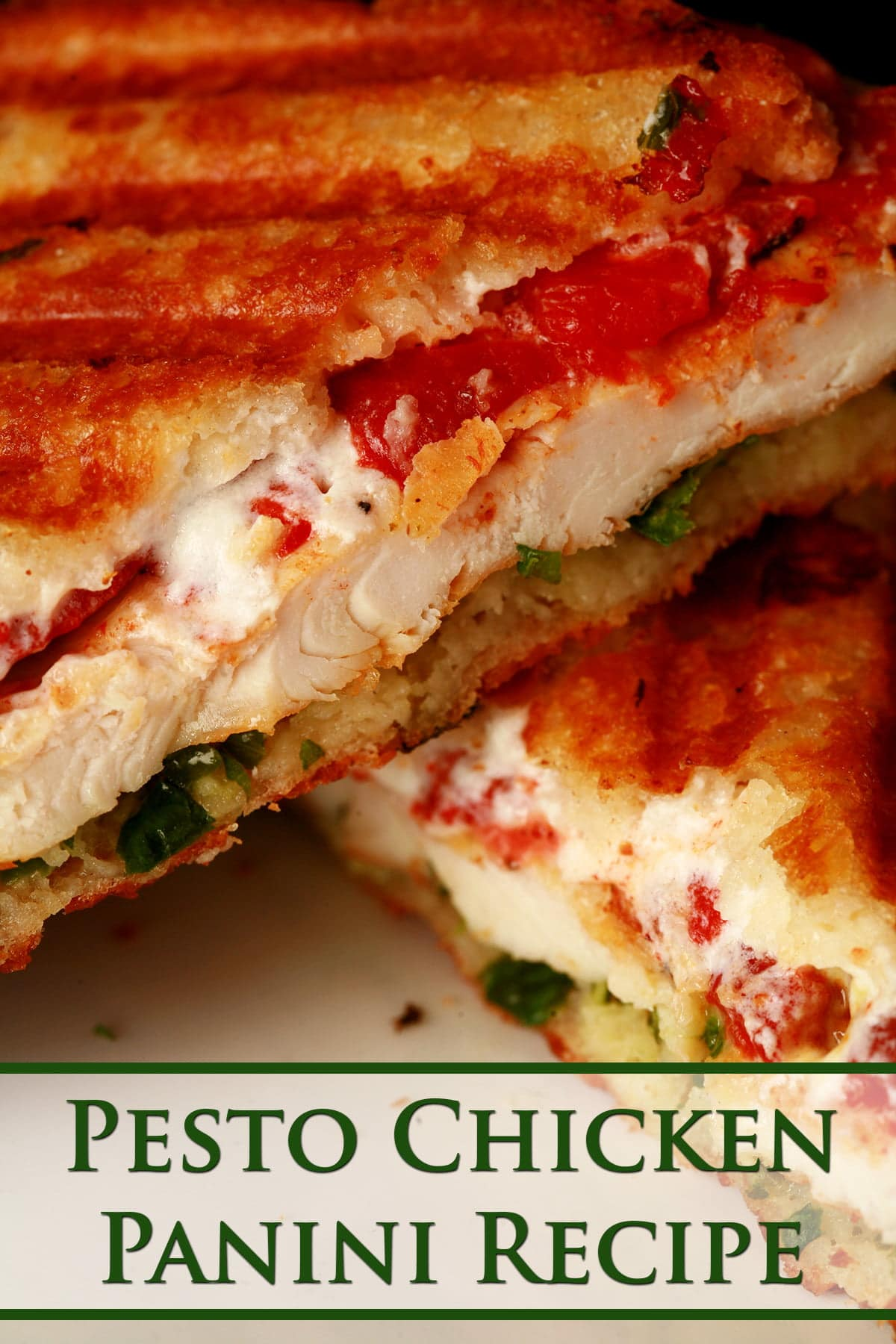 Close up view of a chicken panini sandwich. It's sliced in half, and roasted red pepper, chicken breast, goat cheese, and pesto layers are visible.